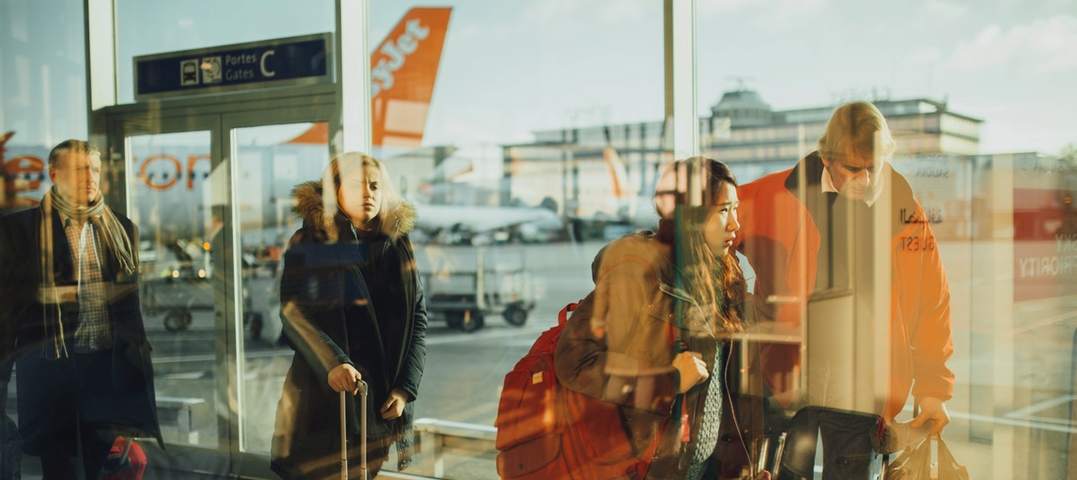 Des clients marchant dans un aéroport avec un EasyJet en fond